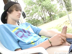 Cute teen guy is sitting outdoors and pleasuring hot masturbation