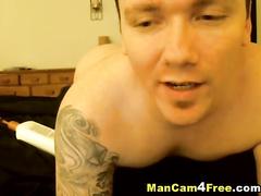 Tattooed hunk in black socks enjoys masturbating dick